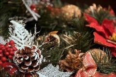 Härligt julpynt: en kotte med snö, ett rött äpple, en guld- kotte och en guld- boll, en röd hårrulle, lögn på granträdet Royaltyfri Foto