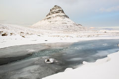 Härligt Kirkjufell berg med snö och den djupfrysta floden på vintern, Island Royaltyfri Bild