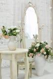 Härligt klassiskt rum med tappningtabellen, vas och blommor, hjärtagarneringar och bilder Royaltyfri Fotografi