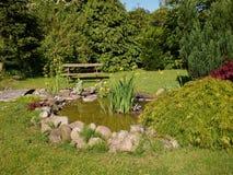 Härligt klassiskt trädgårds- fiskdamm som arbeta i trädgården bakgrund royaltyfri bild