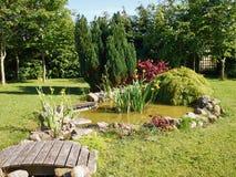 Härligt klassiskt trädgårds- fiskdamm som arbeta i trädgården bakgrund arkivbild