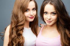 Härligt kopplar samman unga kvinnor i tillfällig kläder över grå bakgrund Skönhet danar ståenden Arkivbilder