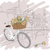 Härligt kort med den nätta cykeln och gula rosor på stadsbakgrund Arkivfoto