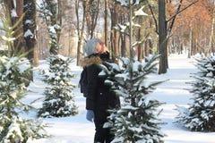 Härligt kvinnaanseende bland snöig träd, i skog och att tycka om för vinter första snö Bärande hatt, plädhalsduk och lag wanderlu arkivbild