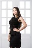 Härligt kvinnaanseende i en svart klänning över dörrar för studiovindhemmiljö bakom Arkivfoto