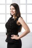 Härligt kvinnaanseende i en svart klänning över dörrar för studiovindhemmiljö bakom Arkivbild