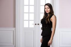 Härligt kvinnaanseende i en svart klänning över dörrar för studiovindhemmiljö bakom Royaltyfri Foto