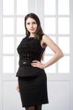 Härligt kvinnaanseende i en svart klänning över dörrar för studiovindhemmiljö bakom Arkivfoton