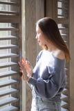 Härligt kvinnaanseende på ett träfönster arkivbild