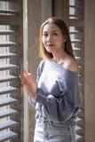 Härligt kvinnaanseende på ett träfönster royaltyfri foto
