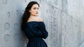 Härligt kvinnaanseende vid den gråa moderna väggen Royaltyfria Bilder