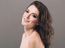 Härligt kvinnaframsidaslut upp ung studio för stående på grå färger Royaltyfri Foto