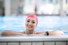 Härligt kvinnalock som ler att se till kameran på gränsen av simbassängen Arkivbilder