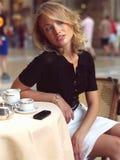 Härligt kvinnasammanträde i ett kafé med mobil s Royaltyfria Foton