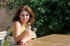 Härligt kvinnasammanträde i ett kafé som dricker kaffe Royaltyfri Foto