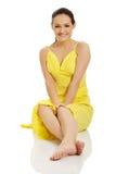 Härligt kvinnasammanträde i gul klänning Royaltyfri Fotografi