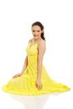 Härligt kvinnasammanträde i gul klänning Fotografering för Bildbyråer