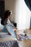 Härligt kvinnasammanträde på en lyxig säng arkivfoto