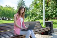 Härligt kvinnasammanträde på en parkerabänk genom att använda en bärbar dator royaltyfri foto