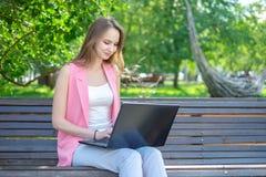 Härligt kvinnasammanträde på en parkerabänk genom att använda en bärbar dator arkivbild