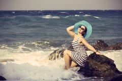 Härligt kvinnasammanträde på en sten och plaska Fotografering för Bildbyråer
