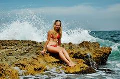 Härligt kvinnasammanträde på en sten och plaska i havet Royaltyfri Bild