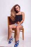 Härligt kvinnasammanträde på en stol i kortslutningsjeans Royaltyfri Bild
