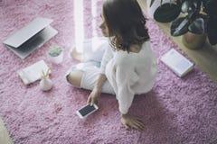 Härligt kvinnasammanträde på rosa färger mattar på golvet på modern och ljus färgad vardagsrum med elektroniska grejer Royaltyfria Foton