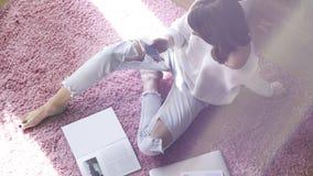 Härligt kvinnasammanträde på rosa färger mattar på golvet på modernt ljus färgad vardagsrum och att använda elektroniska grejer Arkivbild