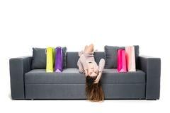 Härligt kvinnasammanträde på soffan med många shoppingpåsen runt om att agera som var glat och som var lyckligt med armar, fördel Arkivbilder