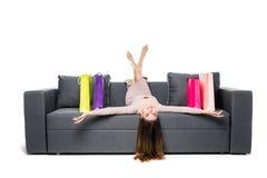 Härligt kvinnasammanträde på soffan med många shoppingpåsen runt om att agera som var glat och som var lyckligt med armar, fördel Royaltyfria Bilder