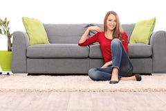 Härligt kvinnasammanträde vid en soffa på golvet royaltyfria bilder