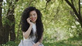 Härligt kvinnasamtal vid telefonen i gräsplanträdgård arkivfilmer
