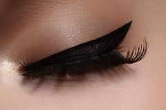 Härligt kvinnligt öga med extrema långa ögonfrans, svart eyelinermakeup Perfekt smink, långa snärtar Closeupmodeögon royaltyfria foton