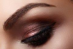 Härligt kvinnligt öga med extrema långa ögonfrans, svart eyelinermakeup Perfekt smink, långa snärtar Closeupmodeögon royaltyfri fotografi