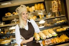 Härligt kvinnligt bageri som poserar med olika typer av smörgåsar Arkivfoto