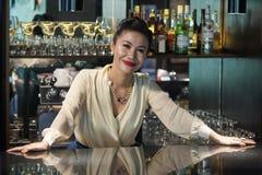 Härligt kvinnligt bartenderanseende som kopplas av på räknaren arkivbilder