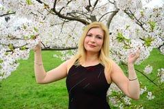 Härligt kvinnligt posera i den sakura trädgården Fotografering för Bildbyråer