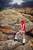 Härligt kvinnligt tecken med två svärd nära de stora stenarna Arkivbild