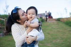 Härligt kyssa för moder som är hennes, behandla som ett barn pojken Arkivfoto