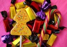 Härligt läckert, sötsaker i mång--färgade packar på en rosa bakgrund Royaltyfri Fotografi