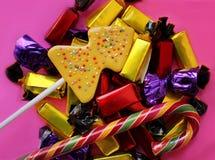 Härligt läckert, sötsaker i mång--färgade packar på en rosa bakgrund Royaltyfri Foto
