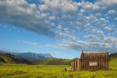 Härligt landskap av blåttskyen, berg och lantlig loge fotografering för bildbyråer