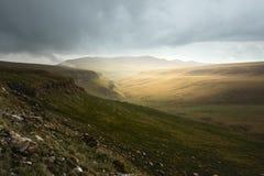 Härligt landskap av det norr Kaukasuset över dalen av berget på solnedgången som ger en härlig färg till fältet Fotografering för Bildbyråer