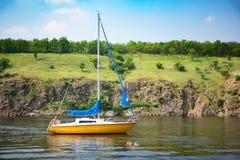 Härligt landskap av seglingyachten med den steniga kusten på backgroun Arkivbild