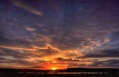 Härligt landskap av sjön och de röda purpurfärgade molnen Royaltyfri Fotografi