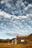 Härligt landskap av skyen, berg och lantlig loge royaltyfria foton
