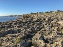 Härligt landskap för stenig strand på den Atlantic Ocean kusten på bakgrund för blå himmel för solsken fotografering för bildbyråer