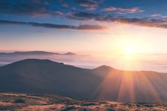 Härligt landskap i bergen på soluppgång Sikt av de dimmiga kullarna som täckas av Retro effekt för skog Resande begreppsbackg royaltyfri fotografi