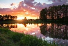 Härligt landskap med brännhet solnedgång över sjön royaltyfri foto